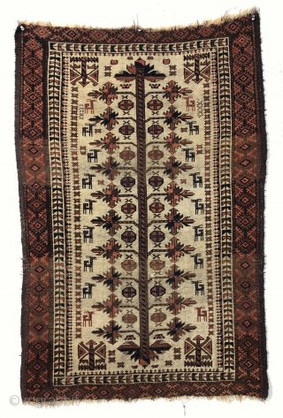 Antique ivory ground Baluch rug with a charming design featuring many good sized animals. The herd of 18 animals (goats? dogs?) flank a traditional Baluch tree motif with interesting corner elements. Overall  ...