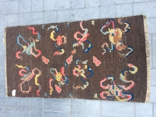 Tibetan rug, brown background with Buddha eight treasures pattern. Wool warp and weft. Good age and condition. Size 150*80cm