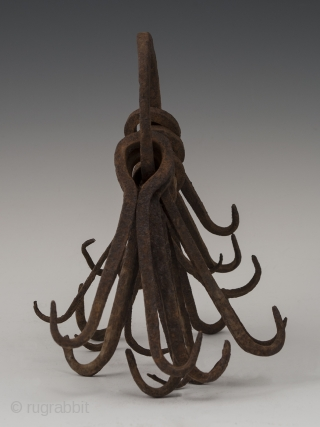 """Ring of double hooks, possibly West Africa. Hand forged iron, 8"""" (20.2 cm) high, Early to mid 20th century.  This might be an unusual type of currency or utilitarian object."""