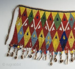 """Pikuran (cache-sexe), Bana Guili people, Mandara Mountains, Cameroon. Seed beads, cotton string, cowrie shells, 19"""" (48.3 cm) wide by 9.5"""" (24 cm) high, mid 20th century or earlier.  The incredible variety of colored  ..."""