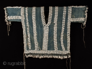 """Ceremonial tunic Bamileke People, Cameroon, West Africa. Hand loomed cotton, cowrie shells, string, leather, 22.5"""" (57 cm) high by 31"""" (79 cm) wide. Mid 20th century."""
