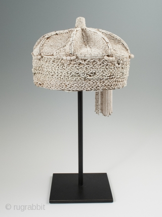 Beaded crown, Yoruba People, Nigeria. 8″ (20.3 cm) high by 7″ (17.8 cm) wide. Mid-20th century. A nice example with two tassels hanging on one side, some slight bead loss and a  ...