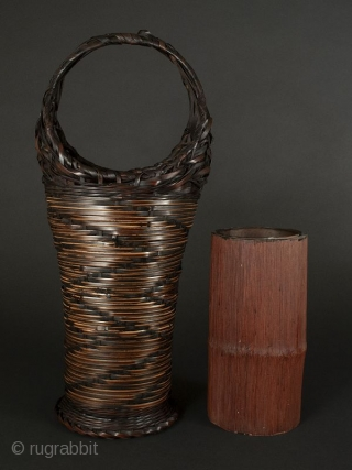 Japanese Antique Bamboo Basket  Japanese antique bamboo basket, tall narrow shape with circular handle. Design on body of zigzag alternating dark woven bamboo on lighter woven material. Ending in circular flattened foot. Interior  ...