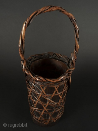 Japanese Antique Bamboo Flower Basket  Japanese antique bamboo flower basket, cylindrical shaped with open weave with a criss cross design. Body open to expose bamboo container. Handle has twisted bamboo strands attached at  ...